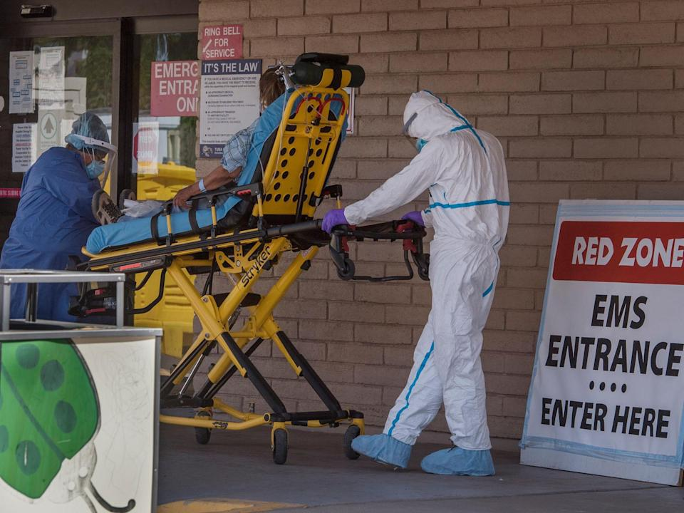 A patient is taken from an ambulance to the emergency room of a hospital in the Navajo Nation town of Tuba City during the 57-hour curfew, imposed to try to stop the spread of the Covid-19 virus: (2020 Getty Images)