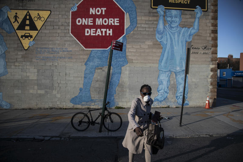 "A woman wearing a mask crosses the street in front of a mural about traffic accidents reading, ""NOT ONE MORE DEATH"" in the Brooklyn borough of New York, March 27, 2020. (AP Photo/Wong Maye-E)"