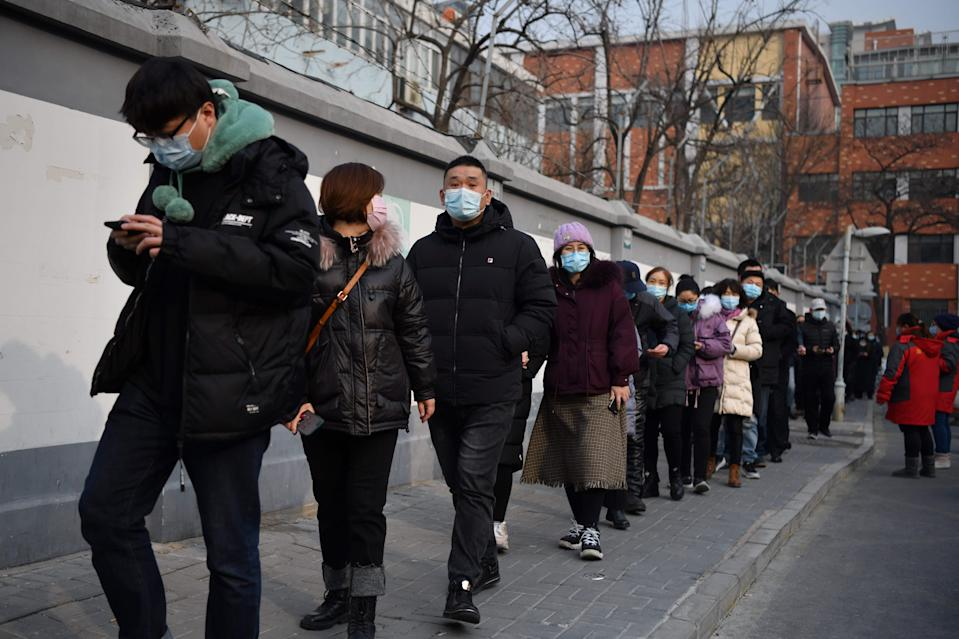 People line up to be tested for the Covid-19 coronavirus in Beijing on January 22, 2021, part of a drive to test two million people in 48 hours as the city rushes to snuff out a new local cluster of cases believed to be linked to a more contagious virus variant. (Photo by GREG BAKER / AFP) (Photo by GREG BAKER/AFP via Getty Images)