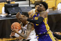 LSU's Mwani Wilkinson, right, fouls Missouri's Xavier Pinson, left, as he shoots during the second half of an NCAA college basketball game Saturday, March 6, 2021, in Columbia, Mo.(AP Photo/L.G. Patterson)