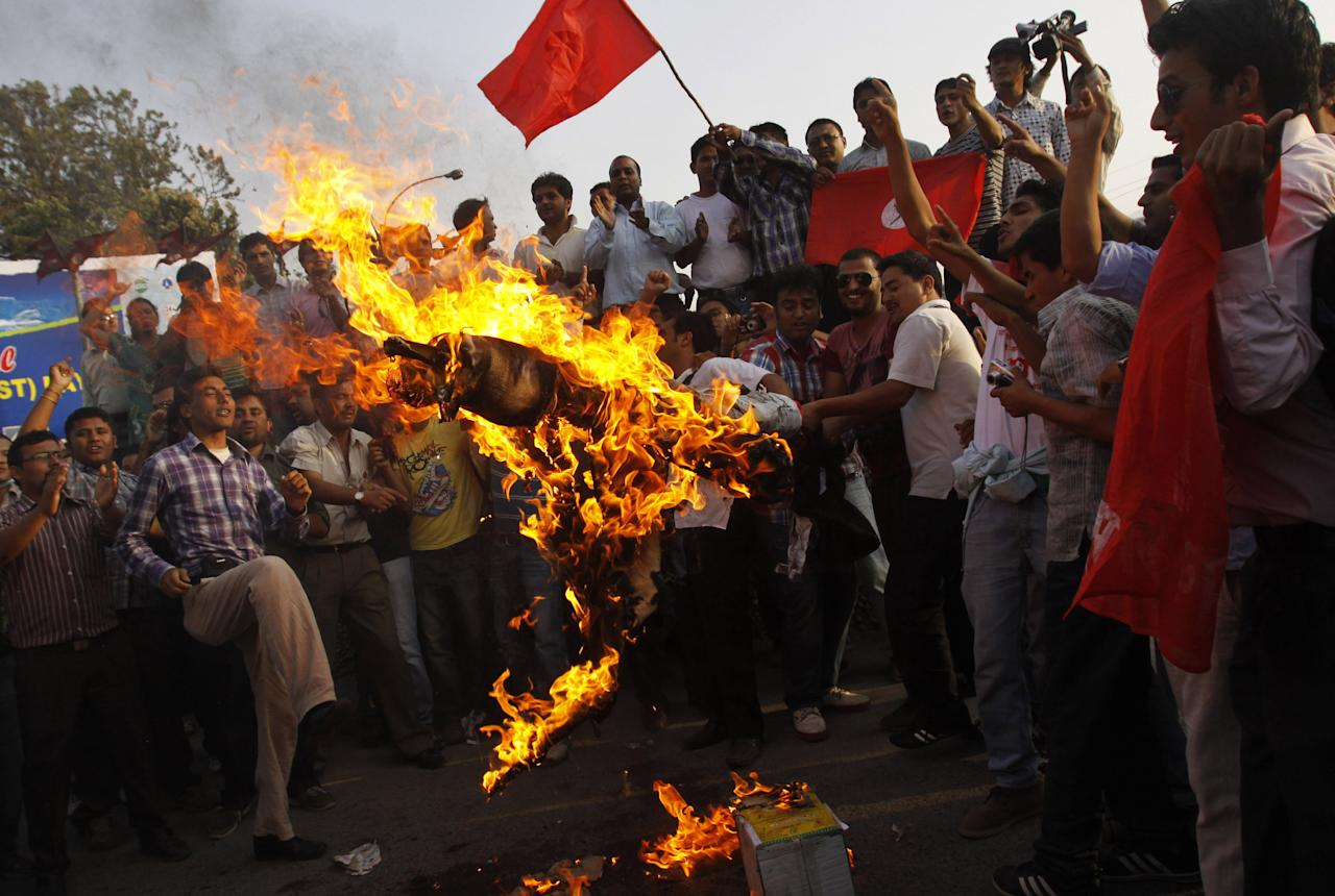 Activists of Nepali Congress affiliated Nepal Students union burn an effigy of Prime Minister Baburam Bhattarai as they demand his resignation in Katmandu, Nepal, Monday, May 28, 2012. Nepal sank into political turmoil Monday after lawmakers failed to agree on a new constitution, leaving the country with no legal government. The premier called new elections, but critics said he lacked the power to do so. (AP Photo/Binod Joshi)