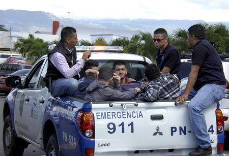 Policemen escort five Syrian men after they were detained at Toncontin international airport in Tegucigalpa, Honduras, November 18, 2015. Honduran authorities have detained five Syrian nationals who were trying to reach the United States using stolen Greek passports, but there are no signs of any links to last week's attacks in Paris, police said. The Syrian men were held late on Tuesday in the Honduran capital, Tegucigalpa, on arrival from Costa Rica, and had been planning to head to the border with neighboring Guatemala. The passports had been doctored to replace the photographs with those of the Syrians, police said. REUTERS/Stringer EDITORIAL USE ONLY. NO RESALES. NO ARCHIVE.