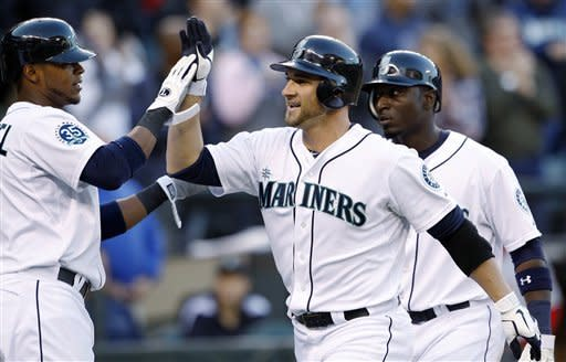 Seattle Mariners' Casper Wells, center, is congratulated by Carlos Triunfel, left, and Trayvon Robinson on his three-run home run against the Los Angeles Angels in the seventh inning of a baseball game Wednesday, Oct. 3, 2012, in Seattle. (AP Photo/Elaine Thompson)