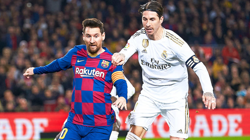 Lionel Messi and Sergio Ramos tussle for the ball.
