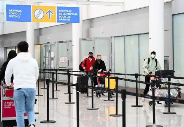 Travellers are directed to take a mandatory COVID-19 test after arriving on a international flight at Pearson International Airport. Starting August 9 fully vaccinated U.S. citizens and permanent residents living in that country will be able to visit Canada without having to quarantine for two weeks. (Nathan Denette/The Canadian Press - image credit)