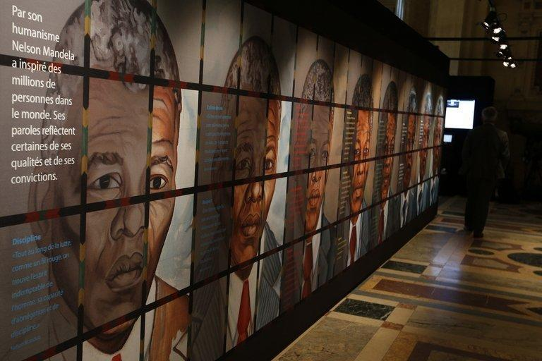 A visitor walks past drawings of Nelson Mandela at an exhibition in Paris on May 29, 2013
