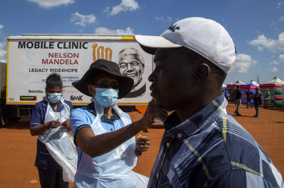 A health worker checks the temperature of a man queueing on a soccer field to be screened and tested for COVID-19 at Lenasia South, south Johannesburg, South Africa, Tuesday, April 21, 2020, during a campaign aimed to combat the spread of Coronavirus. (AP Photo/Themba Hadebe)