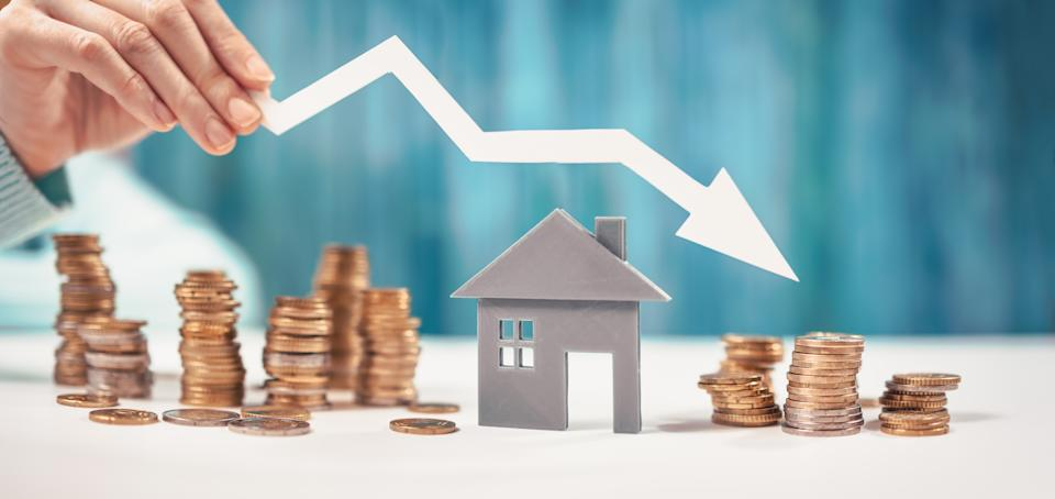 Woman holds an arrow down over model of the house and stack of coins. Concept of the crisis in the real estate market.