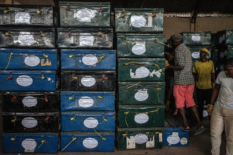 Mozambican Electoral Commission workers load election kit containing ballot boxes and voting material to be shipped out to the countryside at a wharehouse in Maputo on October 13, 2014