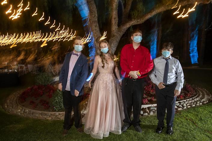 Students in formal clothes and masks in front of a tree with lights.