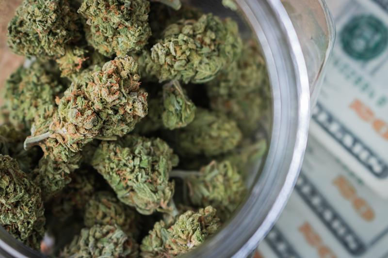 A clear jar packed with cannabis buds that's sitting atop a fanned pile of twenty dollar bills.