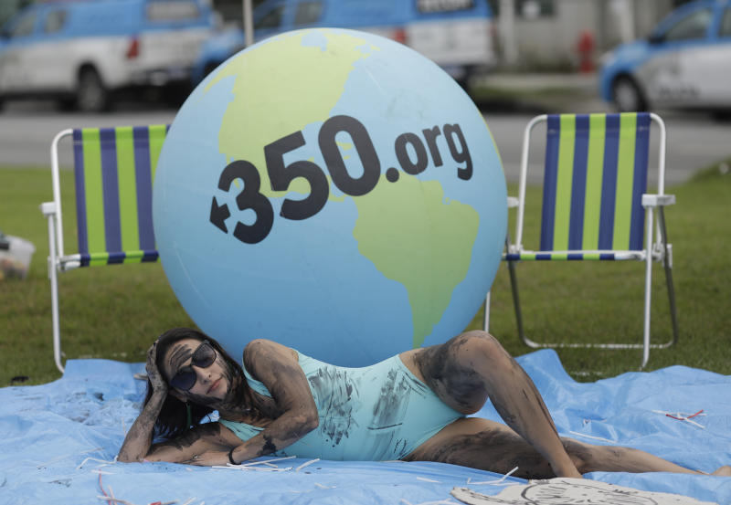 A demonstrator painted with fake oil lies on a tarp during a protest against the auction for the exploration of oil fields close to Abrolhos, a marine national park in Bahia state, in front of the Grand Hyatt Hotel where the auction is taking place, in Rio de Janeiro, Brazil, Thursday, Oct. 10, 2019. Under pressure from environmental organizations, none of the 17 companies involved in the process presented any offers. (AP Photo/Silvia Izquierdo)