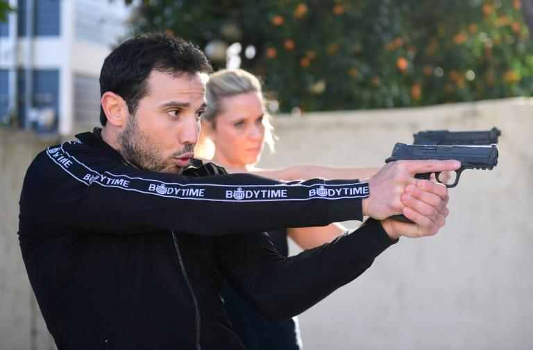Stuntman Daniel Locicero (L) demonstrates the proper grip and technique for using a weapon for actress Courtney M. Moore during a training session in Los Angeles -- stuntmen have long lobbied for their own Oscar category