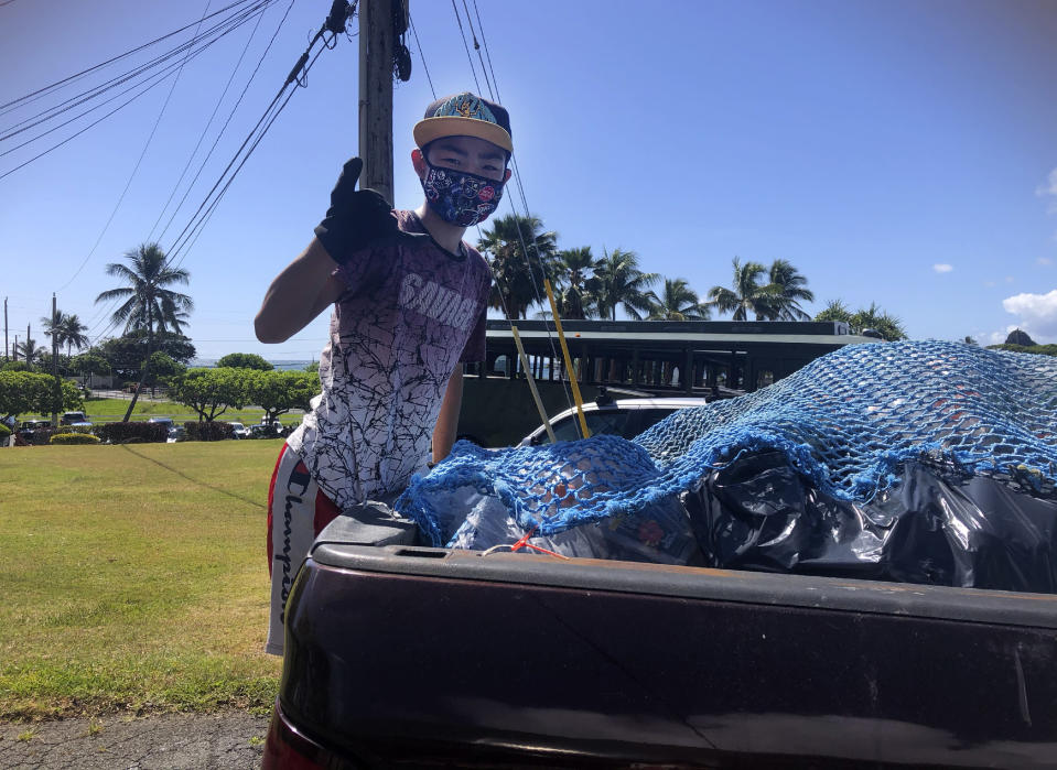 In this May 2021 photo provided by Maria Price, Genshu Price stands on the back of a truck after loading it with recyclable cans and bottles from Kualoa Ranch in Kāne'ohe, Hawaii, for his fundraiser, Bottles4College. (Bottles4College Price via AP)