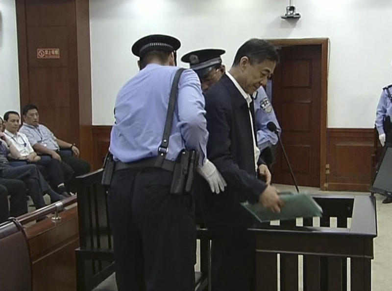In this image taken from video, former Chinese politician Bo Xilai, center, is escorted by court guards before he sits at a defendant's seat for his trial at Jinan Intermediate People's Court in Jinan, eastern China's Shandong province, Sunday, Aug. 25, 2013. Bo on Sunday sought to discredit his former top aide as a lying, unreliable witness as the ousted leader denied criminal responsibility in the country's messiest political scandal in decades.decades. (AP Photo/CCTV via AP Video) CHINA OUT, TV OUT