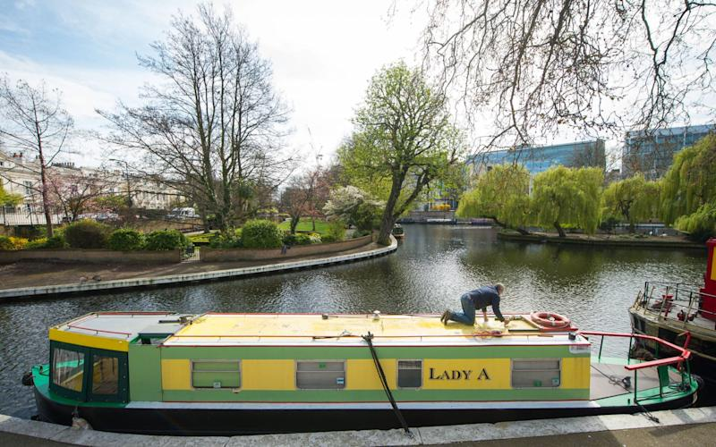 A man works on a narrowboat in Little Venice, London - Credit: Dominic Lipinski/PA