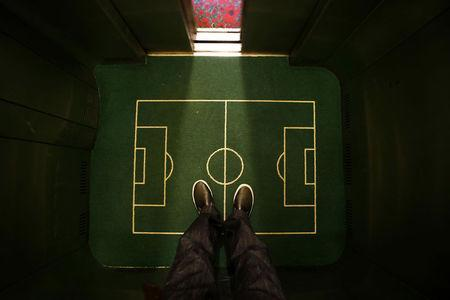 A floor cover depicting a soccer pitch is seen in an elevator in a hotel in Curitiba city June 17, 2014. REUTERS/Ivan Alvarado