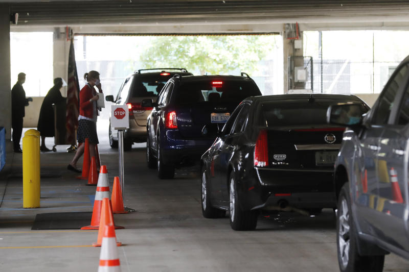 In this  June 26, 2020 photo, cars line up during a drive-thru naturalization service in a parking structure at the U.S. Citizenship and Immigration Services headquarters on Detroit's east side. The ceremony is a way to continue working as the federal courthouse is shut down due to Coronavirus. The U.S. has resumed swearing in new citizens but the oath ceremonies aren't the same because of COVID-19 and a budget crisis at the citizenship agency threatens to stall them again.  (AP Photo/Carlos Osorio)