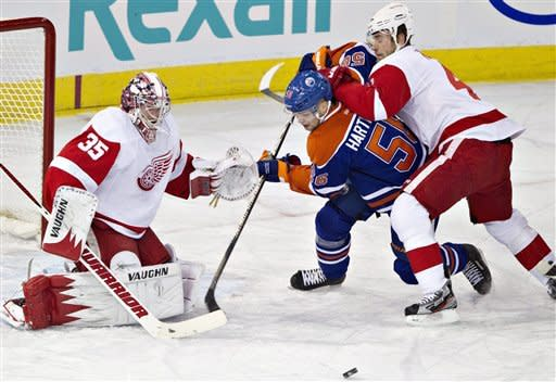 Detroit Red Wings goalie Jimmy Howard (35) makes the save on Edmonton Oilers' Teemu Hartikainen (56) as Jakub Kindl (4) defends during the first period of an NHL hockey game Friday, March 15, 2013, in Edmonton, Alberta. (AP Photo/The Canadian Press, Jason Franson)