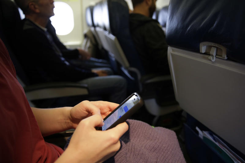 FILE - In this Thursday, Oct. 31, 201 file photo, a passenger checks her cell phone after boarding a flight, in Boston. For the past decade fliers haven't been able to use electronic devices while planes are below 10,000 feet because they might interfere with cockpit instrument, but the Federal Aviation Administration declared Thursday Nov. 21, 2013, that interference isn't a concern anymore. (AP Photo/Matt Slocum, File)