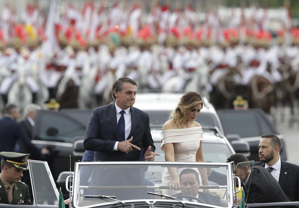 FILE - In this Jan. 1, 2019 file photo, Brazil's President Jair Bolsonaro points with his fingers to mimic guns as he rides in an open car with his wife, first lady Michelle Bolsonaro, after his swearing-in ceremony in Brasilia, Brazil. Bolsonaro's pro-gun position was a trademark of his seven terms as a lower house lawmaker. In July 2018, he shocked adversaries by teaching a toddler how to make the finger-gun sign that came to represent his presidential campaign. (AP Photo/Andre Penner, File)