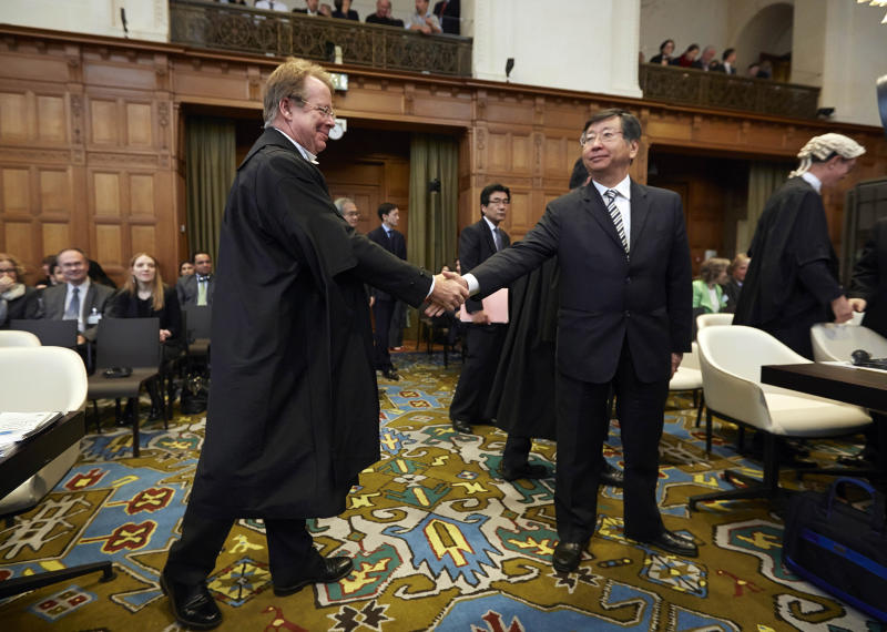 Japanese Ambassador to the Netherlands, and Chief Negotiator, Koji Tsuruoka, center, shakes hand with General Counsel of Australia Bill Campbell, left, before the International Court of Justice to deliver its verdict in The Hague, Netherlands, Monday March 31, 2014. The International Court of Justice is ruling Monday on Australia's challenge against Japan for whaling in Antarctic waters. (AP Photo/Phil Nijhuis)