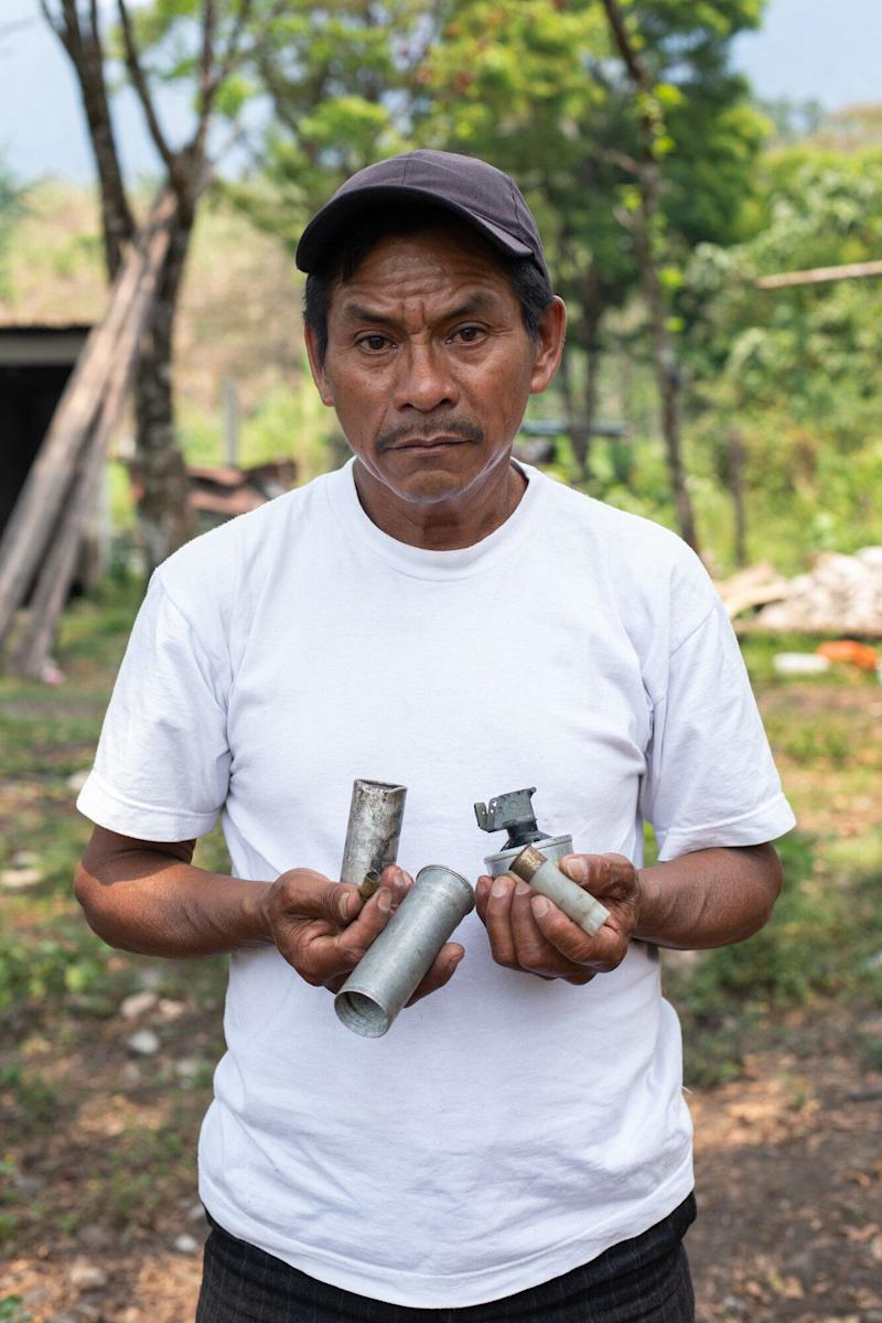 Joel Raymundo Domingo, 55, photographed in April, holds smoke bombs, tear gas canisters and other projectiles used by Guatemalan state forces to disperse a peaceful blockadeagainst the San Mateo Hydroelectric Project, in October 2018. (Photo: Global Witness / James Rodriguez)