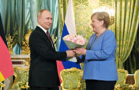 Russian President Vladimir Putin, left, presents flowers to German Chancellor Angela Merkel during their meeting in the Kremlin in Moscow, Russia, Friday, Aug. 20, 2021. The talks between Merkel and Putin are expected to focus on Afghanistan, the Ukrainian crisis and the situation in Belarus among other issues. (Sputnik, Kremlin Pool Photo via AP)