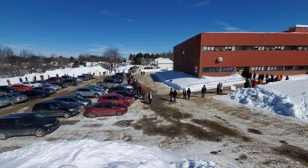 At one point Thursday, more then 120 people were in line outside a Miramichi school waiting for COVID-19 tests, while dozens more were in vehicles stretching down a nearby street.  (Shane Fowler/CBC - image credit)