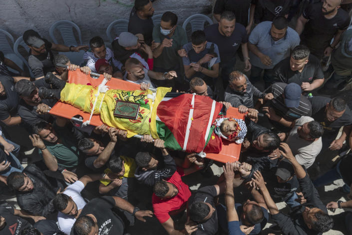 Palestinian mourners carry the body of Ahmed Jamil Fahed during his funeral, in the West Bank refugee camp of al-Amari, Ramallah, Tuesday, May 25, 2021. Fahed was shot and killed by undercover Israeli forces early Tuesday near Ramallah, according to the Palestinian Authority's official Wafa news agency. (AP Photo/Nasser Nasser)