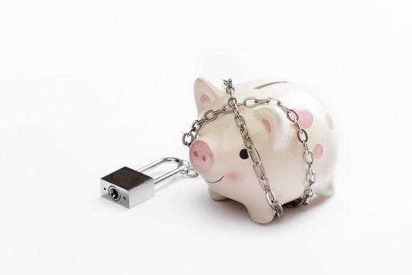 A piggy bank wrapped in a chain with a padlock