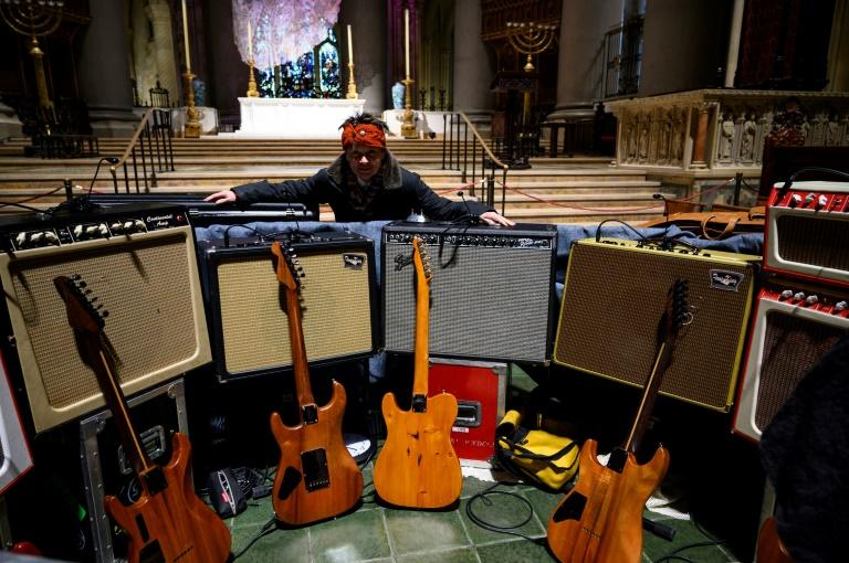 Musician and artist Laurie Anderson, Reed's widow, stands in front of his amps and guitars