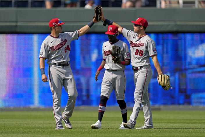 Minnesota Twins outfielders Trevor Larnach (24), Max Kepler (26) and Nick Gordon celebrate after their baseball game against the Kansas City Royals Sunday, July 4, 2021, in Kansas City, Mo. The Twins won 6-2. (AP Photo/Charlie Riedel)