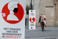 A woman walks past a sign announcing the mandatory use of masks amid the coronavirus disease outbreak in Brussels