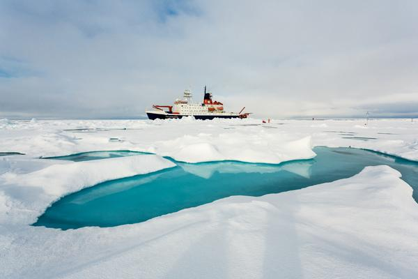 The German research ice breaker RV Polarstern next to a typical sea ice melt pond.