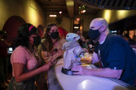 Bartender Guy Klender, right, shares a light moment with customers while celebrating Star Wars Day at Scum and Villainy Cantina, a bar located on Hollywood Blvd, in Los Angeles, Tuesday, May 4, 2021. California has the lowest infection rate in the country. Los Angeles County, which is home to a quarter of the state's nearly 40 million people and has endured a disproportionate number of the state's 60,000 deaths, didn't record a single COVID-19 death Sunday or Monday, which was likely due to incomplete weekend reporting but still noteworthy. (AP Photo/Jae C. Hong)