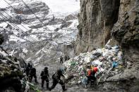 Artisanal gold miners leave a gold mine after their shift in La Rinconada, in the Andes