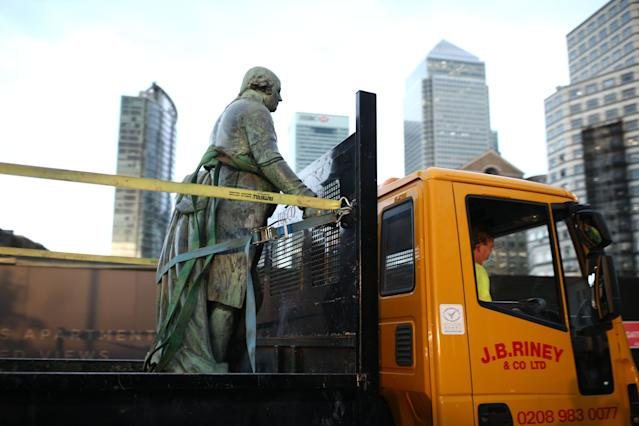 Workers take down a statue of slave owner Robert Milligan at West India Quay. (Getty)