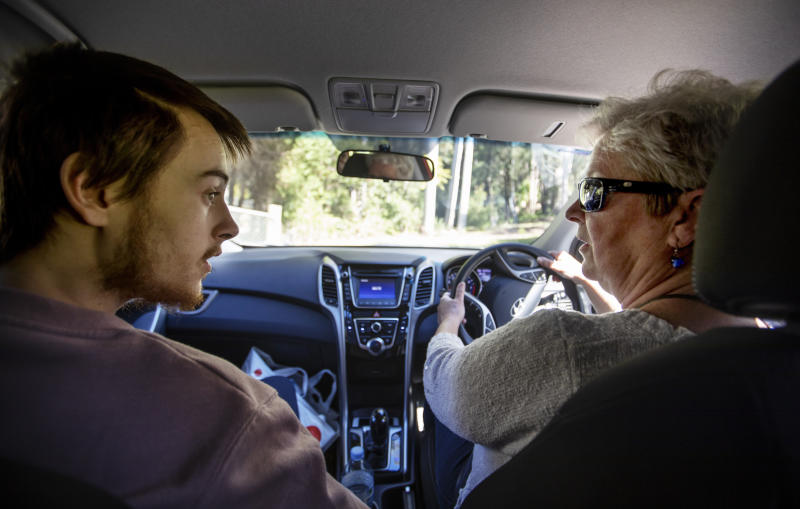 Deb Ware, right, drives her son, Sam, back to her home for the first time since she last found him overdosing there three weeks earlier in Fountaindale, Central Coast, Australia, Friday, July 19, 2019. A couple weeks earlier, he says, he was trying to sleep on the train but couldn't stop crying, thinking about how badly he had hurt his mother. In his bed at the men's shelter in Sydney, he lay awake all night, thinking of her pain. (AP Photo/David Goldman)