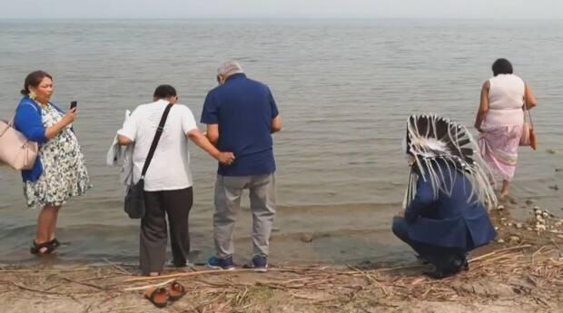 While the annual pilgrimage is being held virtually this year, pilgrims who choose to journey to Lac Ste. Anne to bathe in its waters aren't being turned away.  (Catholic Archdiocese of Edmonton/YouTube - image credit)