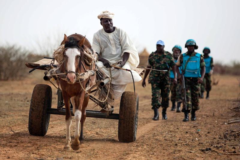 A farmer in Karbab, South Darfur, rides his cart while UNAMID troops from Tanzania arrive at the Sudanese village as part of a routine patrol on July 1, 2014 (AFP Photo/Albert Gonzalez Farran)