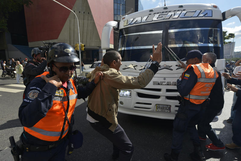 An opposition supporter argues for traffic cops to stop blocking buses carrying opposition lawmakers to the National Assembly in Caracas, Venezuela, Tuesday, Jan. 7, 2020. Opposition leader Juan Guaidó and lawmakers who back him pushed their way into the legislative building on Tuesday following an attempt by rival legislators to take control of the congress, and declared Guaidó the president of the only opposition-controlled institution. (AP Photo/Matias Delacroix)