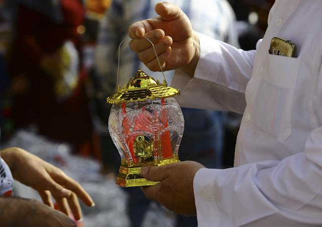 <p>An elderly man checks a traditional Ramadan lantern before buying it to mark the holy month of Ramadan at the main market in Gaza City, May 25, 2017. (AP Photo/Adel Hana) </p>