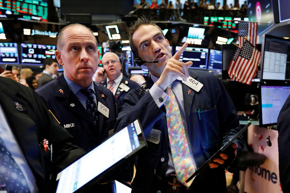 FILE - In this April 18, 2019, file photo traders Michael Urkonis, left, and Gregory Rowe, right, work on the floor of the New York Stock Exchange. The U.S. stock market opens at 9:30 a.m. EDT on Thursday, April 25. (AP Photo/Richard Drew, File)
