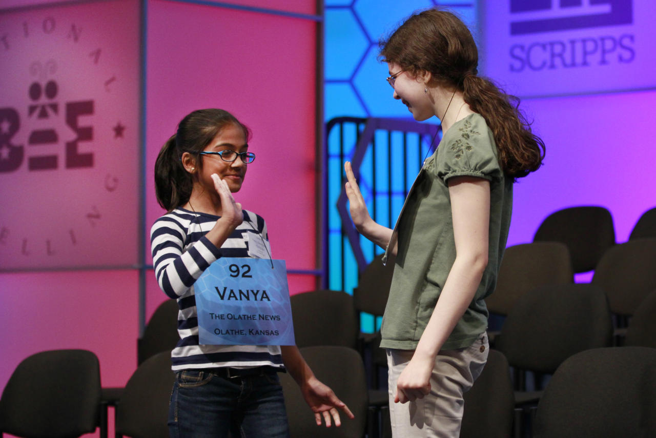 Vanya Shivashankar, 10, of Olathe, Kan., left, and Lena Greenberg, 14, of Philadelphia, high-five after being announced as two of the 50 semifinalists in the National Spelling Bee in Oxon Hill, Md., on Wednesday, May 30, 2012. Shivashankar, whose sister won the bee in 2009, had the only perfect overall score. (AP Photo/Jacquelyn Martin)