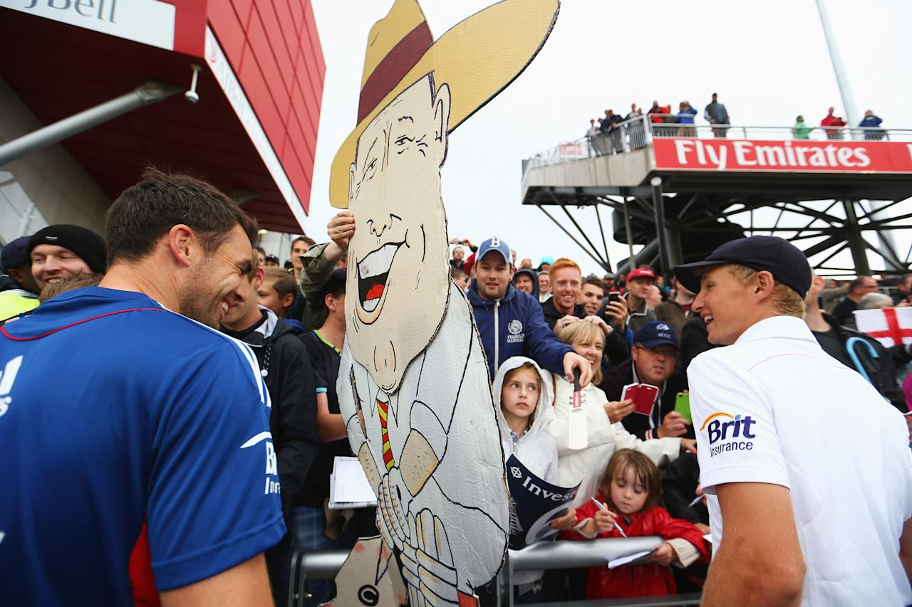 MANCHESTER, ENGLAND - AUGUST 05:  James Anderson (L) and Joe Root of England smile at a cardboard cut-out of Geoffrey Boycott after England retained the Ashes during day five of the 3rd Investec Ashes Test match between England and Australia at Emirates Old Trafford Cricket Ground on August 5, 2013 in Manchester, England.  (Photo by Michael Steele/Getty Images)