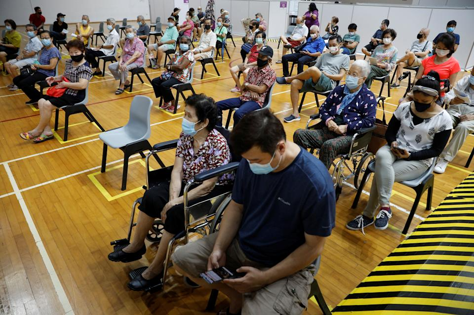 People wait at an observation area after their vaccination at a coronavirus disease (COVID-19) vaccination center in Singapore March 8, 2021. REUTERS/Edgar Su