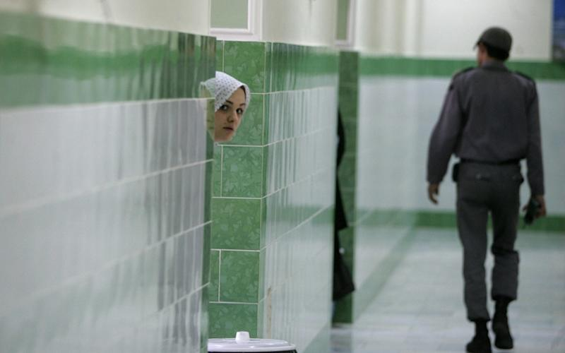 An Iranian inmate peers from behind a wall as a guard walks by at the female section of the infamous Evin jail (file photo) - AFP