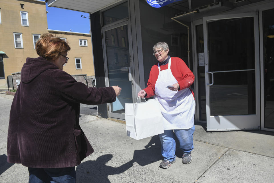 Mildred A. Kennedy, owner of Momma Millie's Bakery, hands Christine Romanko, her blueberry pie, Jewish apple cake and sticky buns order in front of her bakery in Pottsville, Pa., on March 21, 2020. (Jacqueline Dormer/The Republican-Herald via AP)