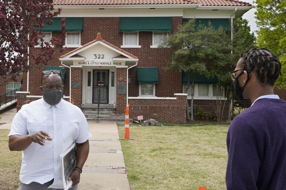 """Chief Egunwale Amusan, stands in front of the Mabel B. Little Heritage House while leading a Black Wall Street tour in Tulsa, Okla., on Monday, April 12, 2021. """"I've read every book, every document, every court record that you can possibly think of that tells the story of what happened in 1921,"""" Amusan told the tour group. """"But none of them did real justice. This is sacred land, but it's also a crime scene."""" (AP Photo/Sue Ogrocki)"""